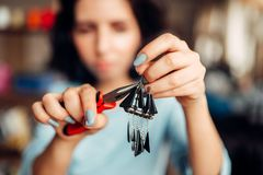 Female master with pliers making handmade earrings. Female person hands with pliers, master making handmade earrings.  Needlework, bijouterie making Stock Photography