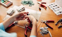 Female person holds pliers, bijouterie making. Female person holds pliers, master at workplace. Handmade jewelry. Needlework, fashion bijouterie making Stock Photo