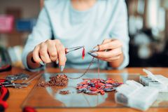 Female person holds pliers, bijouterie making. Female person holds pliers, master at workplace. Handmade jewelry. Needlework, fashion bijouterie making Royalty Free Stock Photos