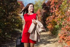 Female person in red dress walking under autumn trees. Young woman with rolling valise on country road in the forest. Female person in red dress walking under stock image