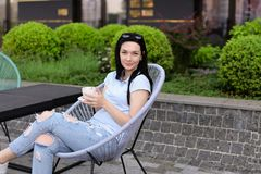 Female person sitting in chair at cafe near green plants and drinking coffee. Concept of leisure time and resting Royalty Free Stock Photo