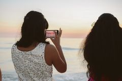 Female Person Taking Cell Phone Picture of the Beautiful Ocean Horizon at Sunset stock images