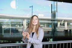 Female person texting by smartphone near valise and airport. Female person typing message by smartphone near valise and airport. Concept of chatting by modern Royalty Free Stock Photos