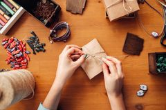 Female person tie a bow on a gift box, needlework. Accessories, top view. Handmade jewelry on wooden table, bijouterie making Stock Photo