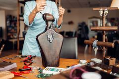 Female person trying on necklace on mannequin. Female person trying on handmade necklace on a wooden mannequin, needlework. Female craftman at the workplace in Stock Photo