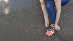 Female person tying laces on sneakers. royalty free stock photography