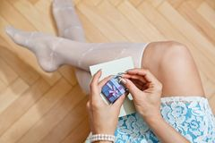 Female person unpacking gift from box. Young woman in elegant high socks and fancy short dress unpacking gift box with a ring. Engaging or Saint Valentine Stock Image