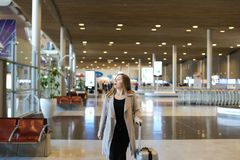Female person wearing grey coat walking in airport hall. Female person wearing grey coat walking in airport hall with valise. Concept of traveling abroad and Stock Photos