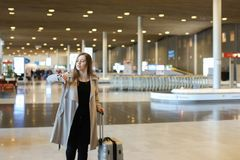Female person wearing grey coat walking in airport hall and looking at watch. Female person wearing grey coat walking in airport hall with valise and looking at Stock Photo