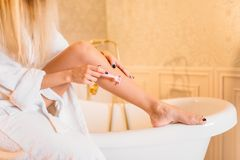 Female person in white bathrobe shaves legs. Bathroom on background, skincare. Bodycare and hygiene, healthcare Royalty Free Stock Image