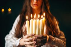 Female person holds candles in hands, divination. Female person in white shirt holds candles in hands. Dark magic ritual, occultism and exorcism, divination Royalty Free Stock Image