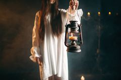 Female person holds kerosene lamp, dark magic. Female person in white shirt holds kerosene lamp in hand. Dark magic ritual, occult and exorcism Royalty Free Stock Photos