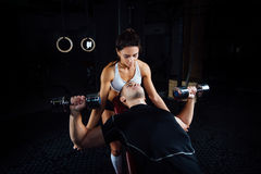 Female personal fitness instructor helping a young man at gym. stock photo