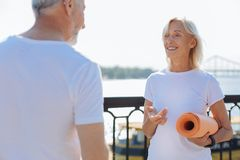 Female personal trainer explaining yoga principles. True professional. Pleasant elderly female personal trainer standing in front of her client, holding an Royalty Free Stock Photos