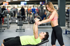 Personal trainer helping a young man lift weights. Female personal trainer helping a young men lift weights while working out in a gym Stock Images