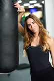 Female personal trainer with punching bag in a gym. Woman wearing sportswear clothes Stock Image