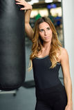 Female personal trainer with punching bag in a gym. Woman wearing sportswear clothes Stock Images