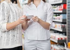 Female Pharmacist Advising Customer Royalty Free Stock Photography
