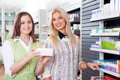 Female Pharmacist Advising Customer At Pharmacy royalty free stock photo