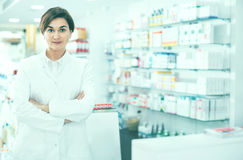 Female pharmacist arranging displayed assortment. Young diligent friendly smiling female pharmacist arranging displayed assortment in pharmacy stock images