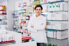 Female pharmacist arranging displayed assortment Royalty Free Stock Image