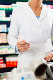 Female pharmacist at the cashier in pharmacy Stock Photo