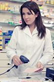 Female pharmacist checking prescription at counter in store Stock Photography