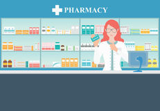 Female pharmacist at the counter in a pharmacy. Royalty Free Stock Photography