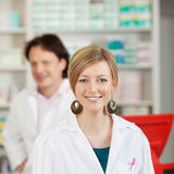 Female Pharmacist With Coworker In Pharmacy Stock Images