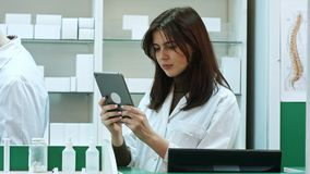Female pharmacist with digital tablet searching for medication stock images