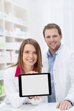 Female pharmacist displaying a blank tablet Stock Photo