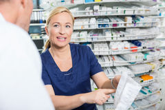 Female Pharmacist Explaining Details Of Product To Royalty Free Stock Photography