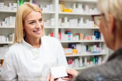 Free Female Pharmacist Explaining Therapy Details To Senior Female Patient Stock Photography - 144743812