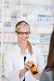 Female pharmacist gives bottle of pills to patient Royalty Free Stock Photography