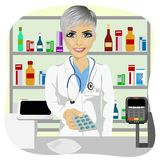 Female pharmacist giving pills in blister pack standing in a drugstore in front of medications on showcase Royalty Free Stock Image
