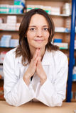 Female Pharmacist With Hands Clasped At Pharmacy Counter Stock Photos