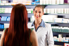 Female pharmacist in her pharmacy with a client Royalty Free Stock Image