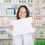 Female Pharmacist Holding Blank Paper At Pharmacy Royalty Free Stock Image