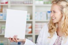 Female Pharmacist Holding Blank Paper Stock Photo