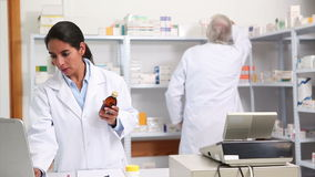 Female pharmacist holding a drug box while smiling Royalty Free Stock Image