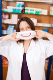 Female Pharmacist Holding Mask With Smiley Stock Photography