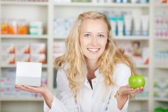 Female Pharmacist Holding Pill Box And An Apple. Portrait of confident female pharmacist holding pill box and an apple in pharmacy Stock Images