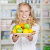 Female Pharmacist Holding Plate Of Fruits Stock Photos