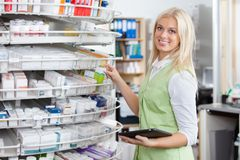 Female Pharmacist Holding Tablet PC. Portrait of female pharmacist holding tablet PC at pharmacy Stock Photography
