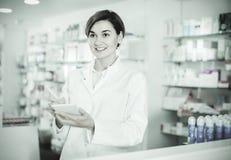 Female pharmacist noting assortment of drugs Royalty Free Stock Photos