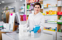 Female pharmacist offering help in choosing at counter in pharma Stock Photos