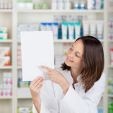 Female Pharmacist Pointing On Blank Paper At Pharmacy Stock Photography