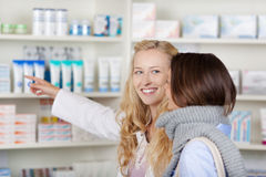 Female Pharmacist Pointing At Medicines While Looking At Custome Royalty Free Stock Photography
