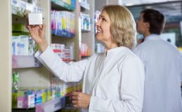Smiling female pharmacist posing in drugstore. Female pharmacist posing near rack in drugstore royalty free stock photography