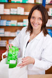Female Pharmacist Putting Medicine Package In Bag At Counter Royalty Free Stock Photography